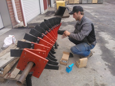 Oskar monterar nya bett på valsen till jordfräsen.