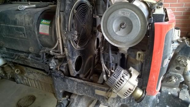 För att komma åt att byta rem måste generatorer och mellanvägg lossas. Eftersom mellanväggen korsas av både bränsleledningar och slangar för luftkonditioneringen kunde den inte lyftas bort......